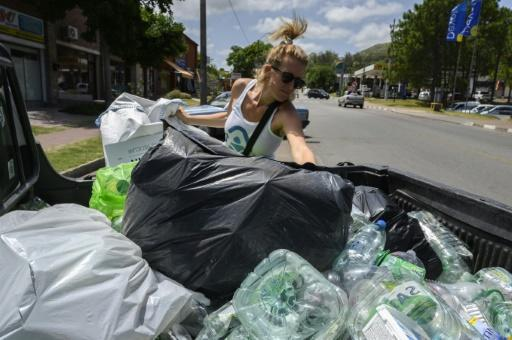 "Nicole Wyaux, co-founder of the ""Plasticoin"" project, fills up a container with plastic waste in Piriapolis, eastern Uruguay"