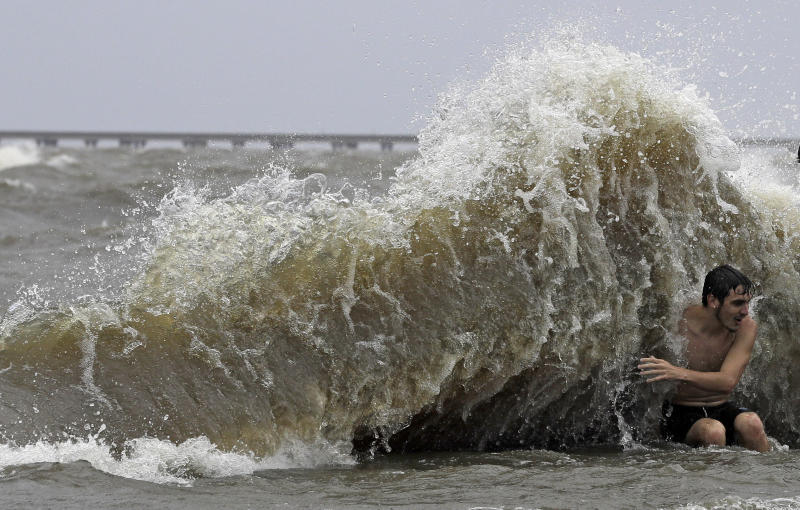 Brady Dayries is hit by a wave as winds from Tropical Storm Barry push water from Lake Pontchartrain over the seawall Saturday, July 13, 2019, in Mandeville, La. (AP Photo/David J. Phillip)
