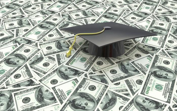 College graduation cap sitting on a bunch of cash