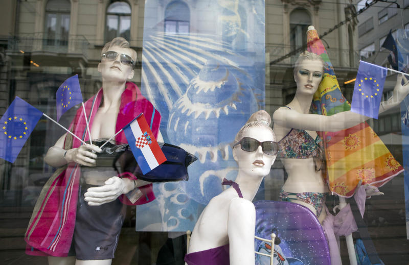 Window mannequins with EU and Croatian flags are on display in a shop window in downtown in Zagreb, Croatia, Sunday, June 30, 2013. Croatia is to join the European Union on July 1, 2013. Fireworks are ready and foreign leaders are arriving as Croatia celebrated on Sunday its entry into the European Union some 20 years after winning independence in a bloody civil war that shook the continent. Croatia will become the 28th EU member on Monday, the bloc's first addition since Bulgaria and Romania joined in 2007. (AP Photo/Darko Bandic)