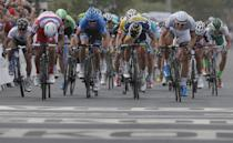 Marcel Kittel of Germany, right in white, sprints towards the finish line ahead of Alexander Kristoff of Norway, second place and second left, and Danny van Poppel of The Netherlands, left of Kittel and third place, to win the first stage of the Tour de France cycling race over 213 kilometers (133 miles) with start in Porto Vecchio and finish in Bastia, Corsica island, France, Saturday June 29, 2013. (AP Photo/Christophe Ena)