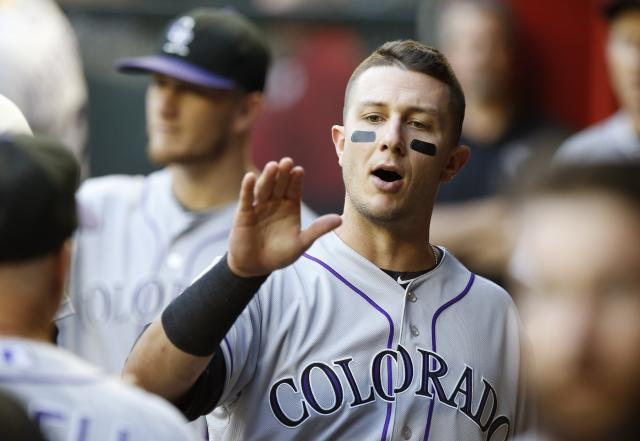 Colorado Rockies' Troy Tulowitzki walks throughout the dugout giving out high-fives prior to a baseball game against the Arizona Diamondbacks on Tuesday, April 29, 2014, in Phoenix. (AP Photo/Ross D. Franklin)