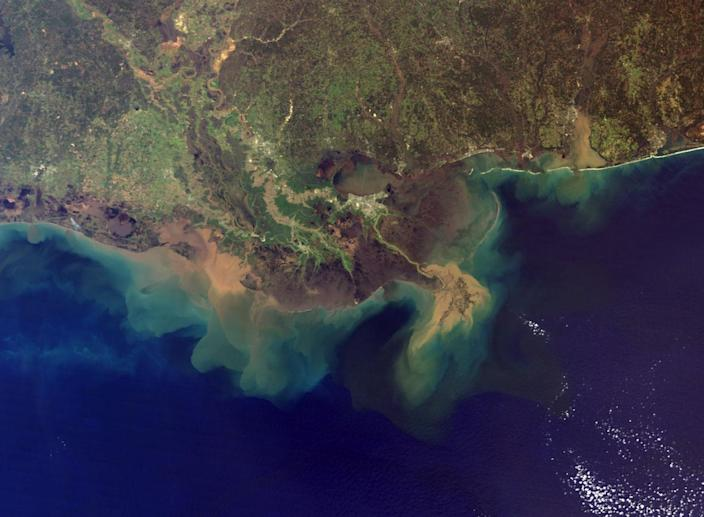 About 500 million tons (550 million metric tons) of sediment flows into the Gulf of Mexico from the Mississippi River each year. This true-color image, acquired from the Moderate Resolution Imaging Spectroradiometer (MODIS) aboard NASA's Terra satellite, shows the murky brown water of the Mississippi mixing with the dark blue water of the Gulf two days after a rainstorm. <cite>NASA</cite>