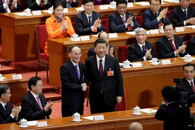 Chinese President Xi Jinping (center R) shakes hands with newly elected Chinese Vice President Wang Qishan at the fifth plenary session of the National People's Congress (NPC) at the Great Hall of the People in Beijing, China March 17, 2018. REUTERS/Jason Lee TPX IMAGES OF THE DAY