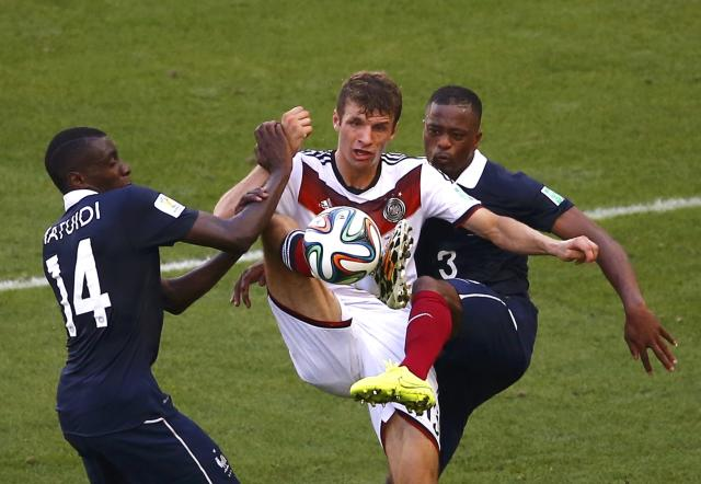 Germany's Thomas Mueller fights for the ball with France's Blaise Matuidi (L) and Patrice Evra during their 2014 World Cup quarter-finals at the Maracana stadium in Rio de Janeiro July 4, 2014. REUTERS/Ricardo Moraes (BRAZIL - Tags: SOCCER SPORT WORLD CUP)