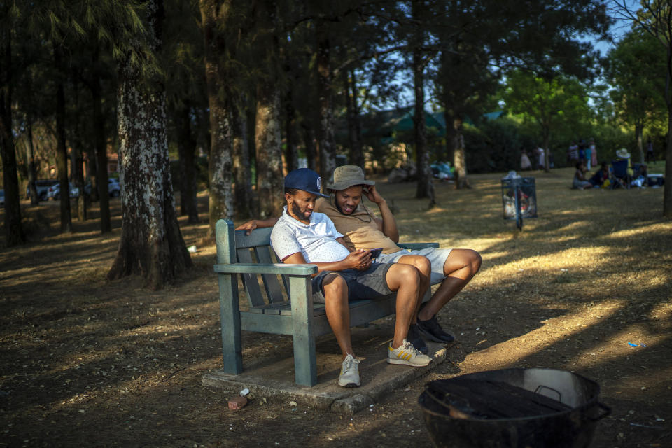 Two men watch a documentary on their cell phone as they join others celebrating South Africa's Heritage Day by cooking a barbecue at Zoo Lake park in Johannesburg Thursday Sept. 24, 2020. As the number of worldwide Covid-19 death is nearing the million mark, coronavirus related case numbers and deaths in South Africa hit the lowest in months. (AP Photo/Jerome Delay)