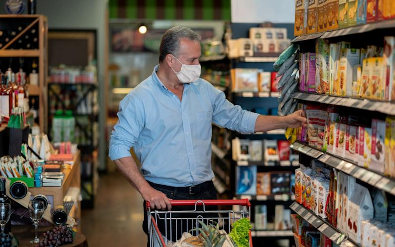 Man grocery shopping at the supermarket wearing a face mask