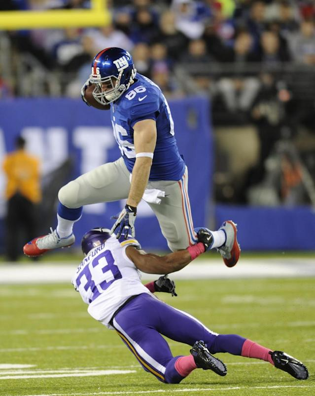 New York Giants tight end Bear Pascoe (86) leaps over Minnesota Vikings' Jamarca Sanford (33) during the first half of an NFL football game Monday, Oct. 21, 2013 in East Rutherford, N.J. (AP Photo/Bill Kostroun)
