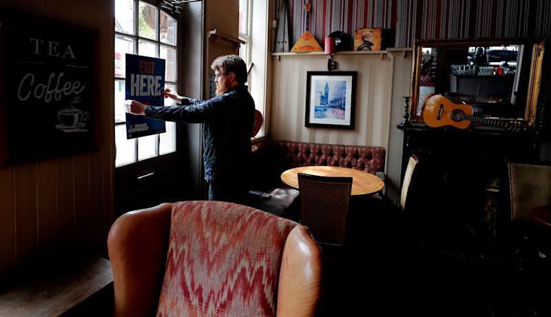 <strong>Signs being put in place instructing on social distancing at the Chandos Arms pub in London</strong> (Photo: ASSOCIATED PRESS)