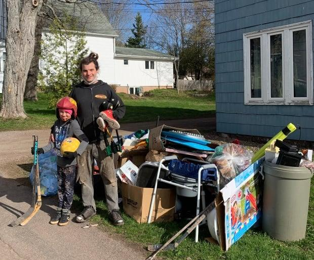 Pete Morouney (left) and Alex Thomas cruise the town looking for hidden gems. This pile provided Pete with two hockey sticks and a ball. (Tori Weldon/CBC - image credit)