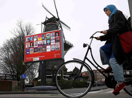 FILE PHOTO: A woman in a headscarf cycles past an election poster billboard and a windmill , the day before a general election, in Amsterdam, Netherlands, March 14, 2017.      REUTERS/Michael Kooren/File Photo