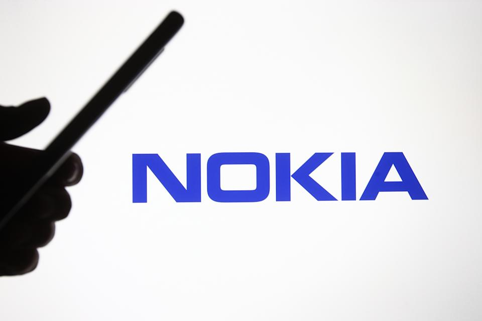 UKRAINE - 2021/02/05: In this photo illustration a Nokia logo is seen in front of a silhouette hand holding a mobile phone. (Photo Illustration by Pavlo Gonchar/SOPA Images/LightRocket via Getty Images)
