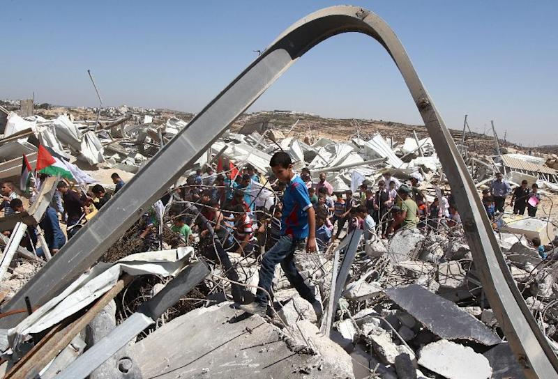 Palestinian students take part in a demonstration amidst the ruins of an Islamic Society dairy factory which was demolished by Israeli authorities earlier this week in the West Bank city of Hebron, on September 4, 2014 (AFP Photo/Hazem Bader)