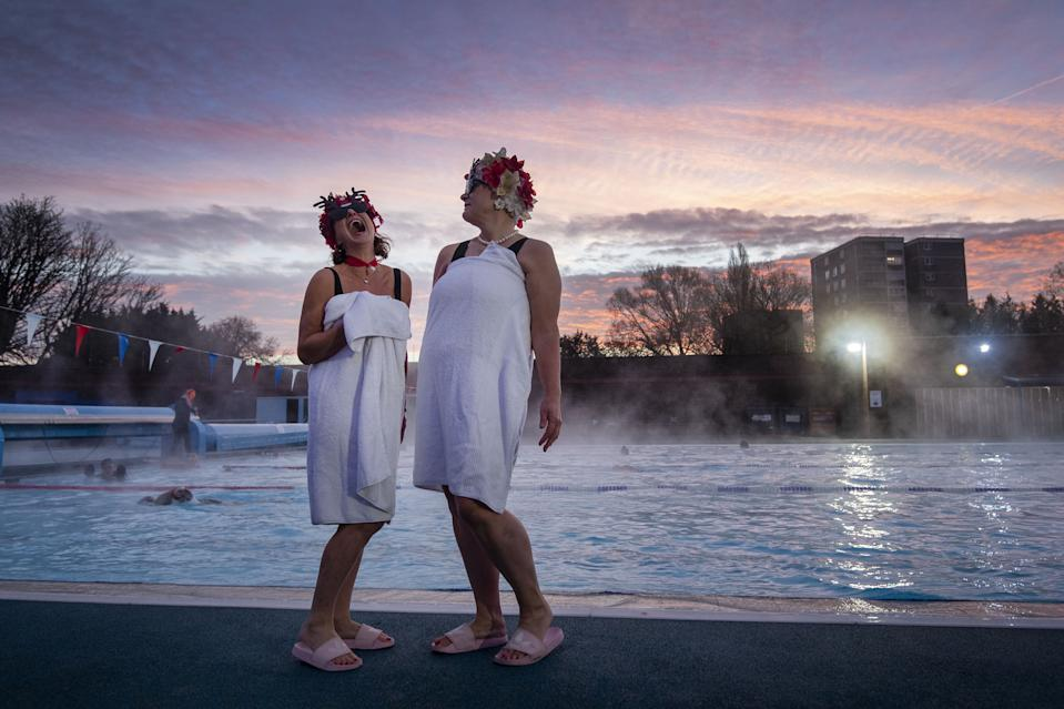 Swimmers known as the Lido Ladies pose by the pool during sunrise at Charlton Lido in Hornfair Park, London, on its first day of reopening after the second national lockdown ended and England enters a strengthened tiered system of regional coronavirus restrictions.