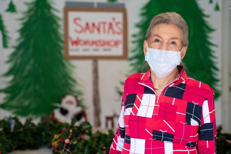 Gwin Dalton stands in the garage at her house in the Wendover-Sedgewood neighborhood. Her daughter, Dede Caughman, created a massive mural inside for a socially distant to-go Christmas.