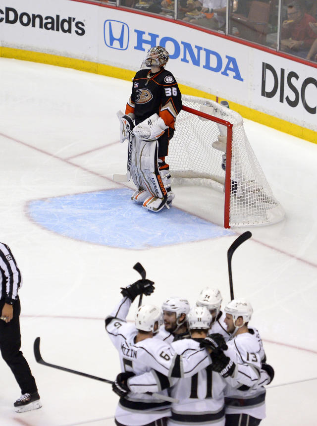 Los Angeles Kings center Anze Kopitar (11), of Slovenia, celebrates his goal with teammates as Anaheim Ducks goalie John Gibson, top, looks up during the second period in Game 7 of an NHL hockey second-round Stanley Cup playoff series, Friday, May 16, 2014, in Anaheim, Calif. (AP Photo/Mark J. Terrill)