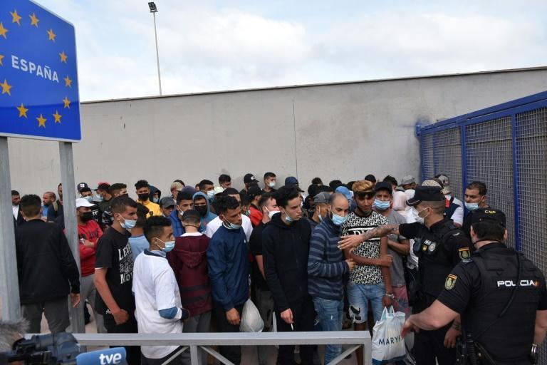 Migrants queue to cross the border back to Morocco at the Spanish enclave of Ceuta