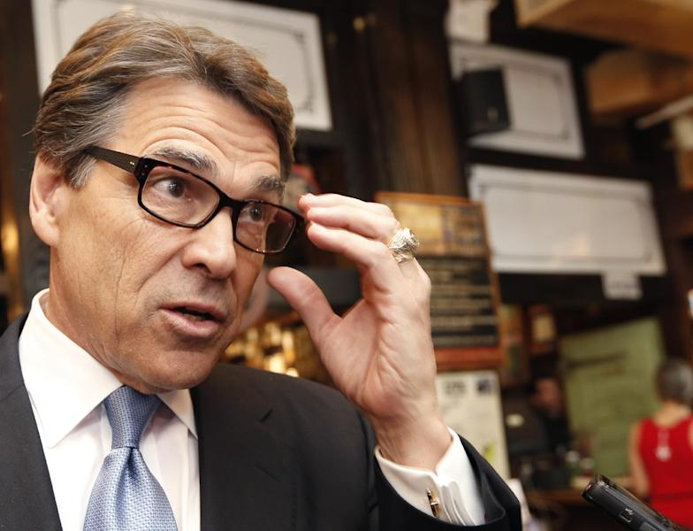 """FILE - In this April 23, 2014 file photo, Texas Gov. Rick Perry speaks to the media after meeting with business owners in New York. Gov. Perry says Tuesday, May 6, 2014, that he never tried making a deal with an Austin district attorney about vetoed state funding that is now the focus of a grand jury investigation. Perry said Tuesday that he would let the case """"play out its course"""" as a grand jury in Austin considers whether the possible 2016 Republican presidential candidate abused his power last summer. (AP Photo/Kathy Willens, File)"""