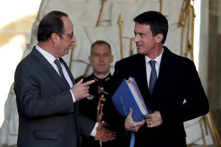 French President Francois Hollande (L) speaks with Prime Minister Manuel Valls as he leaves the Elysee Palace in Paris, France, November 30, 2016 following the weekly cabinet meeting, Picture taken November 30, 2016. REUTERS/Philippe Wojazer/File Photo