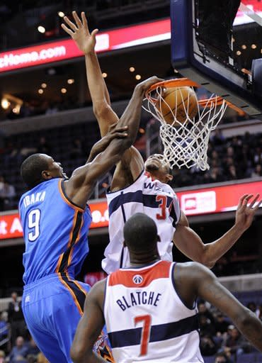 Oklahoma City Thunder forward Serge Ibaka (9), of the Republic of Congo, dunks over Washington Wizards center JaVale McGee (34) and Andray Blatche (7) during the first half of an NBA basketball game on Wednesday, Jan. 18, 2012, in Washington. (AP Photo/Nick Wass)