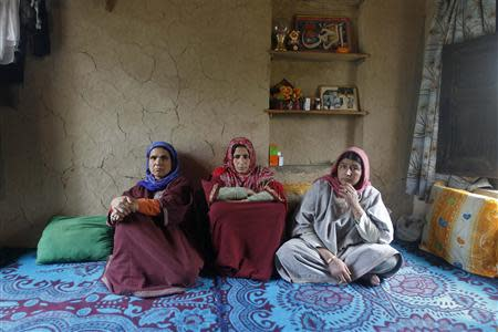 Saheema Akhtar (C), wife of Mohammed Amin Pandith, a village council head, who was killed by militants, sits with relatives inside her house in Gulzarpora, south of Srinagar April 23, 2014. REUTERS/Danish Ismail