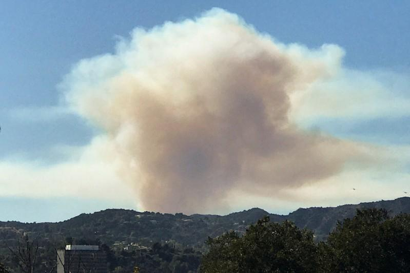 Smoke can be seen as a wild fire breaks out in the hills of Pacific Palisades in Los Angeles, California