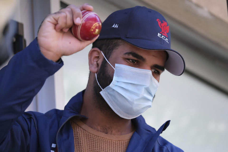 Ali Cheema, a former cricketer from Pakistan, holds a cricket ball after the Rome-based humanitarian group the Baobab Experience arranged for a delivery of cricket gear to migrants in Tuzla, Bosnia, Thursday, May 20, 2021. Among those who sought the gear and who waited eagerly for the packages to arrive was Ali Cheema, who said he started playing cricket when he was 7 and used to play for several clubs in his native Pakistan. Now 24, Cheema has been in Bosnia for the past two years. (AP Photo/Kemal Softic)