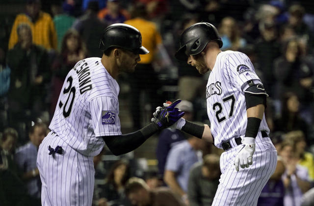 Colorado Rockies' Trevor Story (27) celebrates a solo home run with Ian Desmond (20) during the third inning of a baseball game against the New York Mets, Tuesday, June 19, 2018, in Denver. (AP Photo/Jack Dempsey)