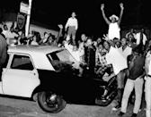 FILE - In this Aug. 12, 1965, file photo, demonstrators push against a police car in the Los Angeles area of Watts. Watts has been associated with an uprising in 1965 that led to burned-down buildings and bloodshed. But when some protests against racial injustice in 2020 devolved into vandalism and looting, Watts has been peaceful. (AP Photo/File)