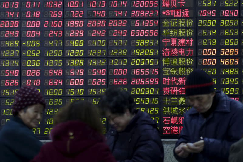FILE PHOTO: Investors stand in front of an electronic board showing stock information on the first trading day after the week-long Lunar New Year holiday at a brokerage house in Shanghai