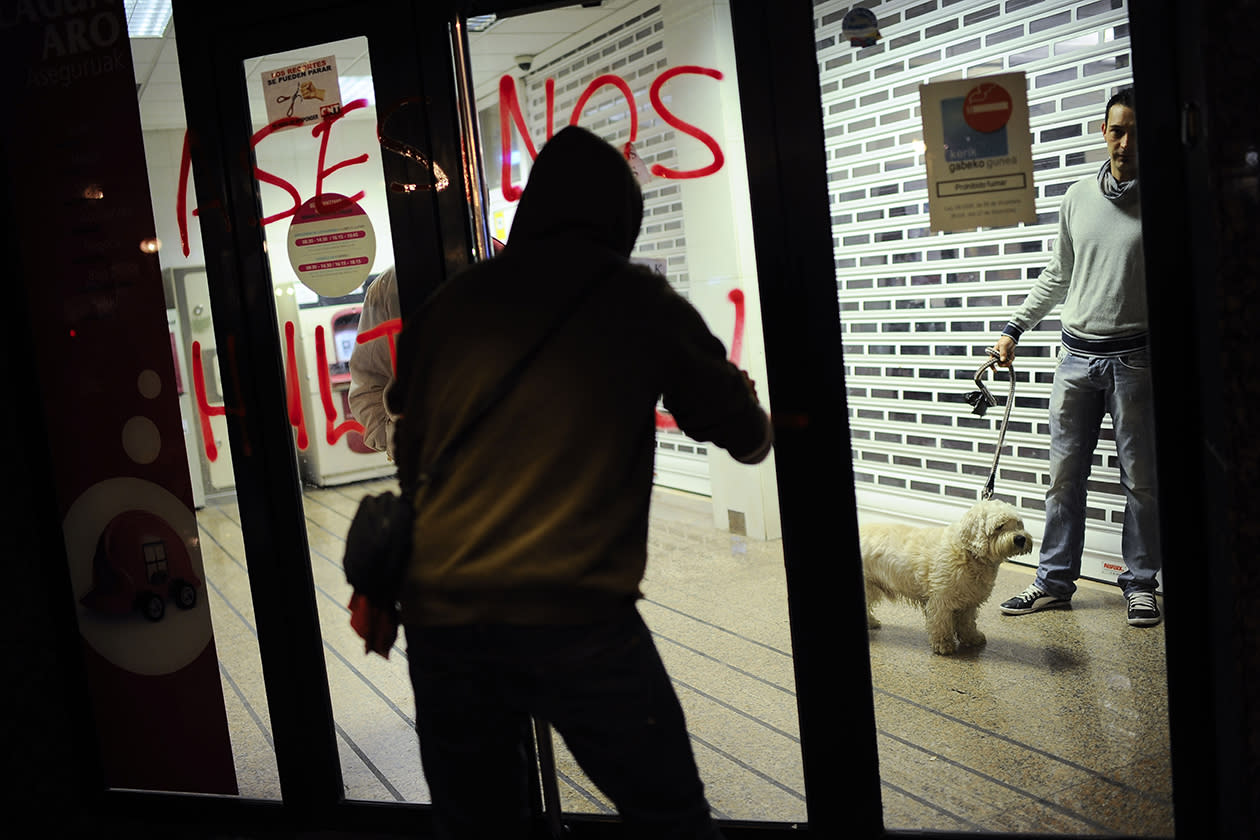 A demonstrator paints a graffiti against banks reading, ''Assassin'' while a man with his dog looks at him , right, from inside a cash dispenser, during a  march against evictions, in Barakaldo, northern Spain.