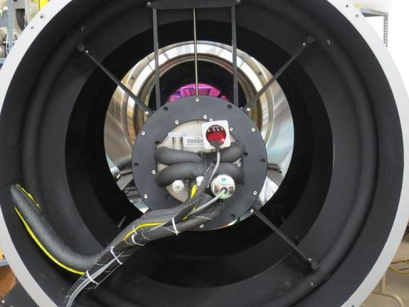 A view down the throat of the DFM telescope with the ATLAS camera mounted on the spider ring. The magenta area is the reflection off of the interference visual filter in front of the ATLAS detector and the primary mirror.