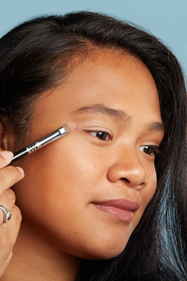 <p>Taking a dense, flat eye-shading brush, pick up the matte beige shade named Solid Gold and buff it across your lids. This base layer will make your crease and lid shadows look more vibrant.</p>