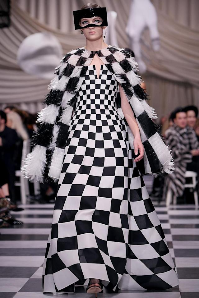 <p>A model wears a black and white checkered feather cape and matching gown from the Dior Haute Couture SS18 collection. (Photo: Getty) </p>