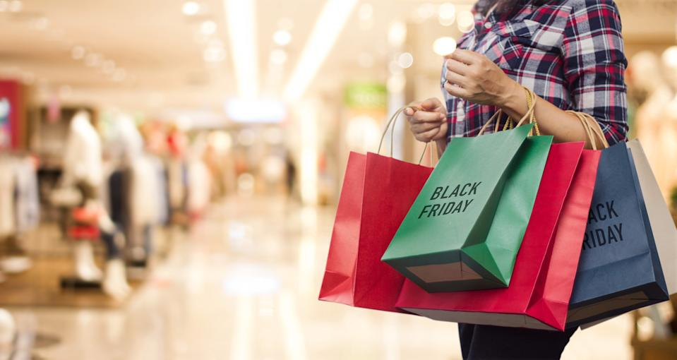 Black Friday, Woman holding many shopping bags while walking in the shopping mall background.