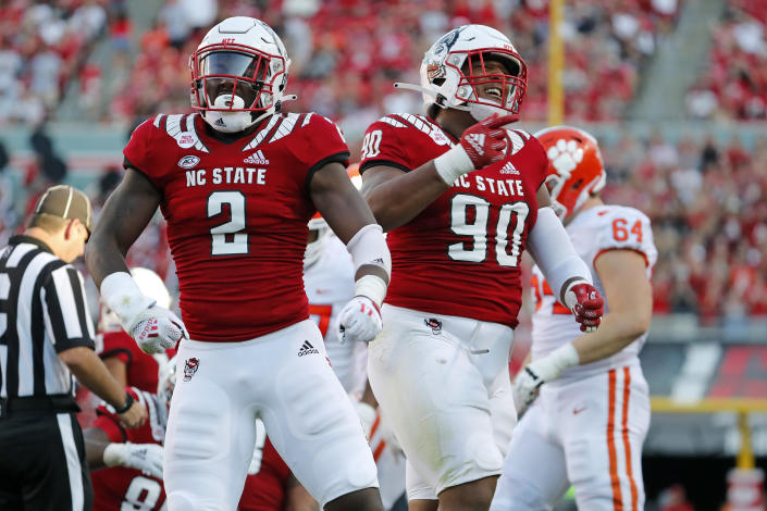 North Carolina State's Jaylon Scott (2) and Savion Jackson (90) celebrate a sack during the second half of an NCAA college football game against Clemson in Raleigh, N.C., Saturday, Sept. 25, 2021. (AP Photo/Karl B DeBlaker)