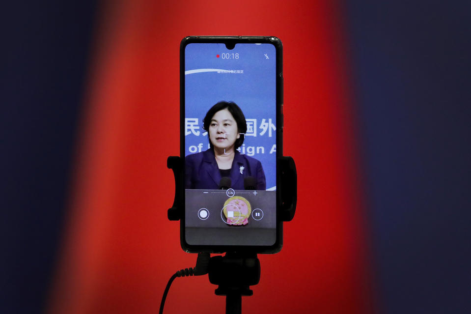"FILE - In this Sept. 1, 2020 file photo, a smartphone records Chinese Foreign Ministry spokeswoman Hua Chunying as she speaks during a daily briefing at the Ministry of Foreign Affairs in Beijing. ""I'd like to stress that if the United States truly respects facts, it should open the biological lab at Fort Detrick, give more transparency to issues like its 200-plus overseas bio-labs, invite WHO experts to conduct origin-tracing in the United States,"" she said at a January 2021 MOFA press conference that went viral in China. (AP Photo/Andy Wong)"