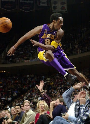 Los Angeles Lakers' Kobe Bryant jumps over a row of fans after saving the ball from going out of bounds in the second half of the Lakers 107-101 win over the Houston Rockets in Houston, Dec. 20, 2001. Bryant, a five-time NBA champion and a two-time Olympic gold medalist, died in a helicopter crash in California on Sunday, Jan. 26, 2020. (AP Photo/Pat Sullivan)