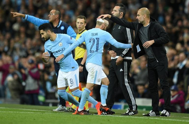 Manchester City's manager Pep Guardiola (R) taps midfielder David Silva on the head as he is substituted for midfielder Ilkay Gundogan during the UEFA Champions League Group F football match against Napoli October 17, 2017