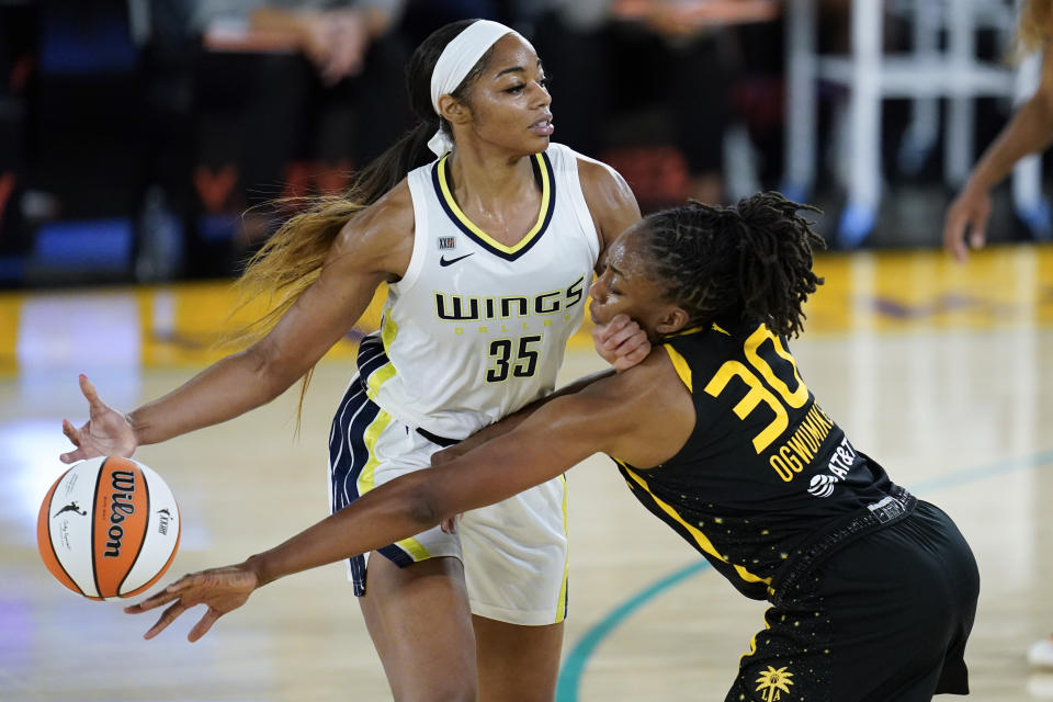 Los Angeles Sparks forward Nneka Ogwumike reaches for the ball controlled by Dallas Wings rookie forward Charli Collier during their game on May 14, 2021 in Los Angeles. (AP Photo/Ashley Landis)