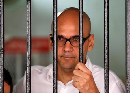 FILE PHOTO: Canadian teacher Neil Bantleman looks out from a holding cell to speak with supporters before the start of his trial at a South Jakarta court in Jakarta