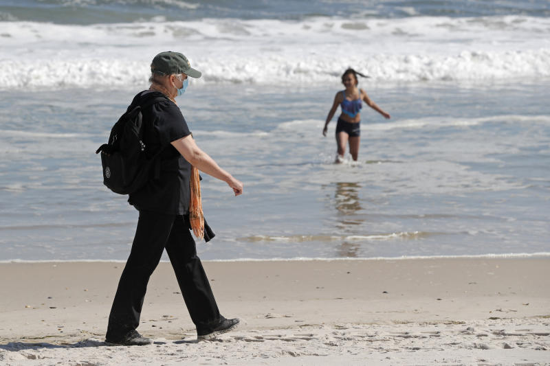 A woman wears a protective face mask during the current coronavirus outbreak, Thursday, May 21, 2020, as she walks on Jones Beach in Wantagh, New York. As pandemic lockdowns ease across the United States, millions of Americans are set to take tentative steps outdoors to celebrate Memorial Day, the traditional start of summer. But public health officials are concerned that if people congregate in crowds or engage in other risky behaviors, the long weekend could cause the coronavirus to come roaring back. (AP Photo/Kathy Willens)