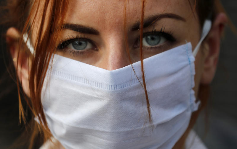 An member of the group 'Pause the System' wears a face mask as she protests in front of the entrance to Downing Street in London, Friday, March 20, 2020. For most people, the new coronavirus causes only mild or moderate symptoms, such as fever and cough. For some, especially older adults and people with existing health problems, it can cause more severe illness, including pneumonia. (AP Photo/Frank Augstein)