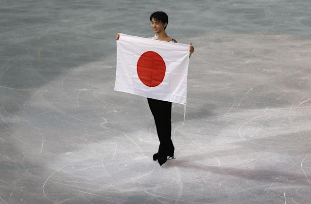 Yuzuru Hanyu of Japan poses with the national flag after he placed first in the men's free skate figure skating final following the flower ceremony at the Iceberg Skating Palace during the 2014 Winter Olympics, Friday, Feb. 14, 2014, in Sochi, Russia. (AP Photo/Darron Cummings)