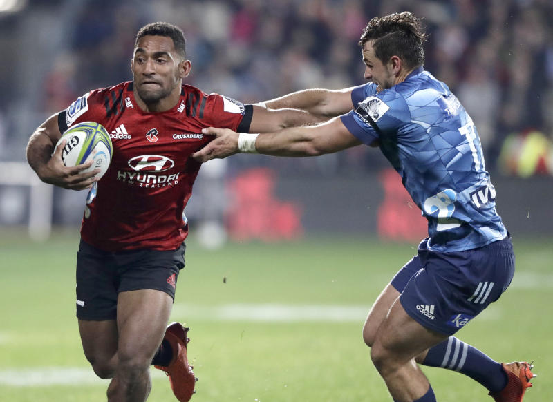 Crusaders Sevu Reece, left, runs at Blues Harry Plummer during the Super Rugby Aotearoa rugby game between the Crusaders and the Blues in Christchurch, New Zealand, Saturday, July 11, 2020. (AP Photo/Mark Baker)