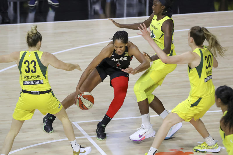 A'ja Wilson dribbles in front of three Storm players.