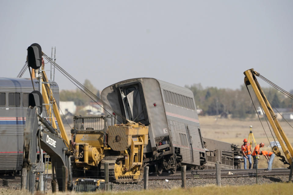 Workers examine a section of railroad track, Sunday, Sept. 26, 2021, next to cars from an Amtrak train that derailed the day before just west of Joplin, Mont., killing three people and injuring others. The westbound Empire Builder was en route to Seattle from Chicago, with two locomotives and 10 cars. (AP Photo/Ted S. Warren)