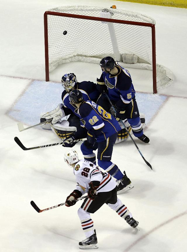 Chicago Blackhawks' Ben Smith (28) scores past St. Louis Blues goalie Ryan Miller, Kevin Shattenkirk (22) and Barret Jackman (5) during the second period in Game 5 of a first-round NHL hockey playoff series Friday, April 25, 2014, in St. Louis. (AP Photo/Jeff Roberson)