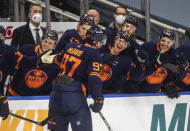 Edmonton Oilers' Connor McDavid (97) celebrates his 100th point this season, against the Vancouver Canucks during the second period of an NHL hockey game Saturday, May 8, 2021, in Edmonton, Alberta. (Jason Franson/The Canadian Press via AP)