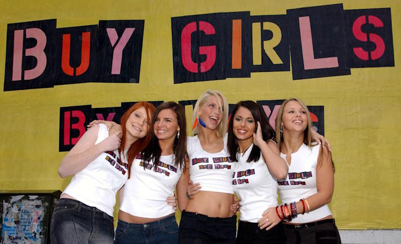 Popstars - The Rivals winners, Girls Aloud from left to right; Nicola Roberts, 17, Nadine Coyle, 17, Sarah Harding, 20, Cheryl Tweedy, 19, and Kimberley Walsh, 20, pose for photographers in front of their poster in east London. (Photo by Ian West - PA Images/PA Images via Getty Images)